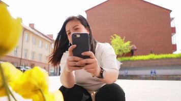 donna asiatica seduta e scattare una foto di fiori su smartphone video