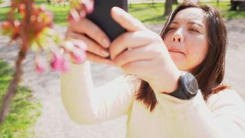 donna asiatica che scatta una foto di fiori sullo smartphone in una giornata di sole video