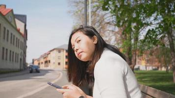 Asian woman sitting at bus stop to wait for a bus with smartphone video