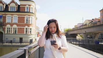 Asian woman walking on a bridge in town and using smartphone video
