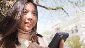 gros plan d'une femme asiatique et d'un visage heureux et utilisant son smartphone video