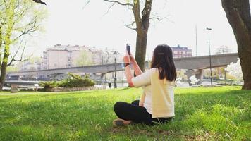 vista posteriore di una donna asiatica che scatta una foto con lo smartphone nel parco cittadino video