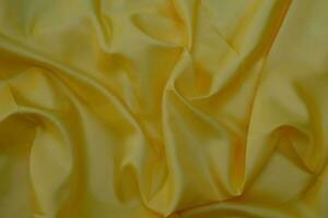 Closeup of smooth elegant yellow silk fabric luxury cloth texture photo