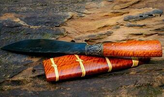 cuchillo personalizado o enep en la vaina de madera natural hecho a mano de tailandia foto