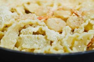 Fried prawns with Italian pasta called mafaldine and parmesan photo