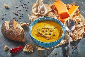 Orange cream soup made of pumpkin, onion, pepper, potato photo