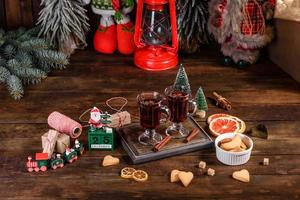 Christmas mulled red wine with spices and fruits on a dark table. photo