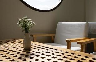 Flores blancas en jarrón sobre mesa de madera foto