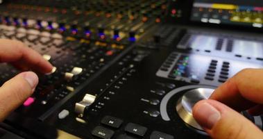 A man working on an audio mixer video