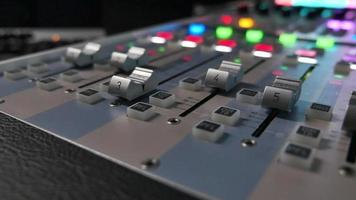 A colorful audio mixers knobs being pulled automatically up and down video