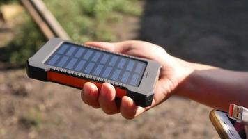 um pacote de energia móvel recarregável com painéis solares em mulheres jovens. video