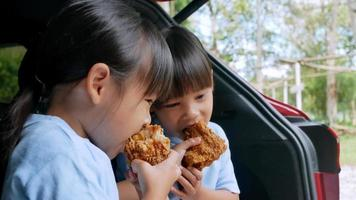 sibling girls having break eating fried chicken in trunk of car. video