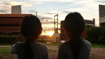 Two sibling sisters eattng sweet tasty ice cream outdoors at sunset. video