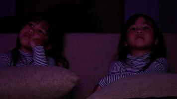 Cute little children sitting on sofa and watching cartoons on TV. video