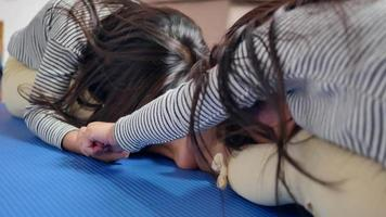 Little cute girls practicing yoga pose on a mat indoors. video