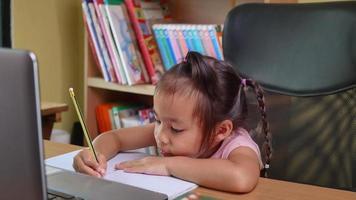 söt liten skolflicka som studerar läxematematik under sin online. video