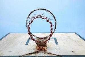 Viejo tablero de baloncesto y cielo azul a la luz del sol foto