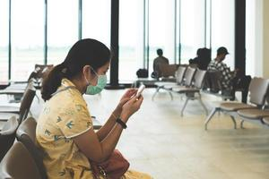 Young asian woman sitting in the airport and wearing face mask photo