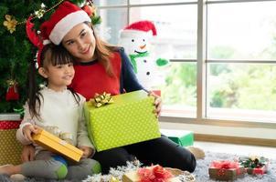 madre asiática le da un regalo de navidad a su hija foto
