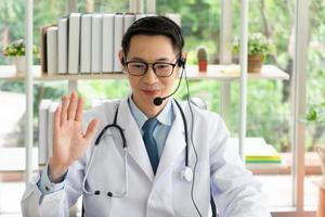 Asian doctor give consult to patient via online video call photo