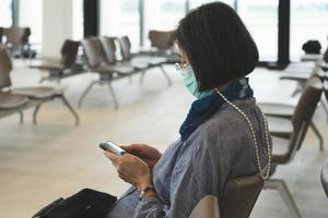 Senior Asian woman wearing mask while sitting in airport photo