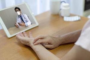 Patient consult asian doctor online via video call photo