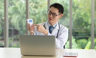 Young Asian doctor give consult to patient online photo