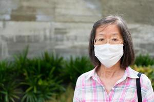 Senior Asian woman wearing mask while going outdoors photo
