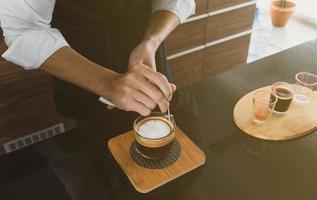 Barista making art coffee latte in cafe photo