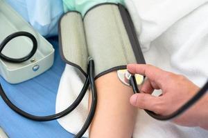 El médico mide la presión arterial del paciente. foto