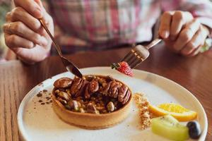 Woman using fork and spoon to eat peanut caramel pie photo