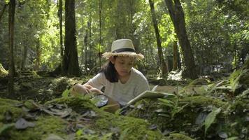 garota escrevendo no caderno sobre a natureza na floresta para a educação. video