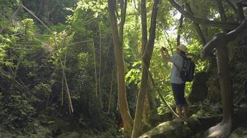 touriste avec sac à dos prenant une photo avec un smartphone en forêt. video