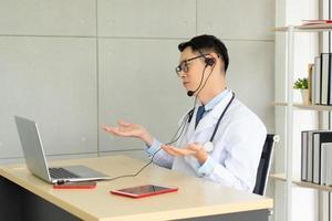 Joven médico asiático asiste a una reunión en línea a través de una videollamada en la oficina foto