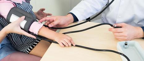 Médico con esfigmomanómetro para medir la presión arterial de la niña. foto