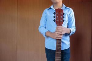 Boy playing classic guitar with fun photo