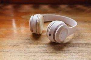White headphones on wooden background. Music concept. photo