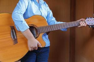 niño tocando la guitarra clásica con diversión foto