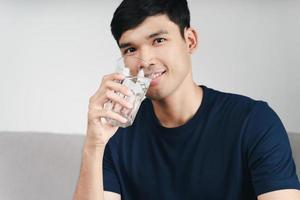 Handsome asian man drinking a glass of water photo