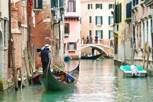 Traditional Venice Cityscape with narrow canal, gondola photo