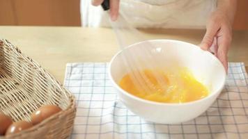 cocinera está batiendo huevos en un recipiente blanco sobre la mesa de madera. video