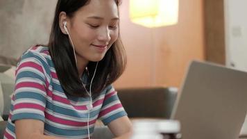 mulher asiática usando laptop para trabalhar em casa e aprendizagem on-line. video