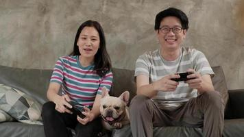 Asian couple is playing video games and pet dog nearby.