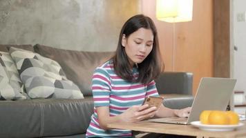 mulher asiática freelance trabalhando em casa com telefone e laptop. video