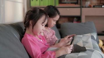 Two Asian girls playing online mobile phone game in living room. video