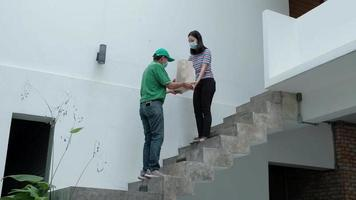 Delivery man with face mask gives parcel to an Asian woman. video