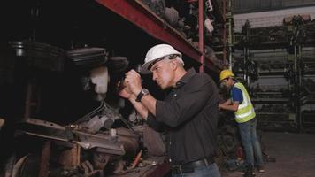 deux ingénieurs masculins vérifiant les pièces du moteur dans une usine d'entrepôt. video