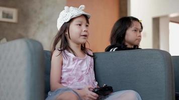 dos chicas asiáticas en ropa casual juegan divertidos videojuegos consola. video
