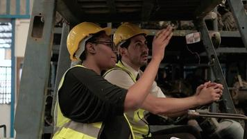 Caucasian male and black female engineers in the forklift truck. video
