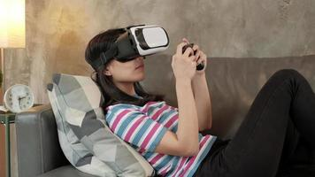 Asian woman with VR glasses headset and game joys controller. video